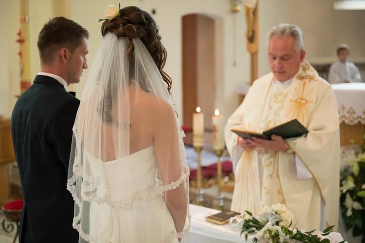 Para młoda przed ołtarzem słucha słów księdza