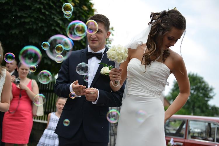 Para młoda po ślubie w kościele wśród baniek mydlanych