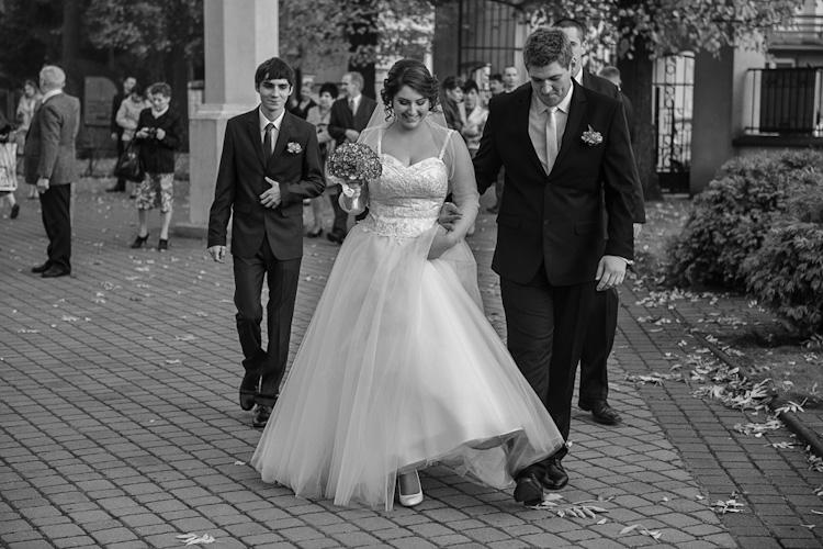 Para młoda przed kościołem w drodze na ślub