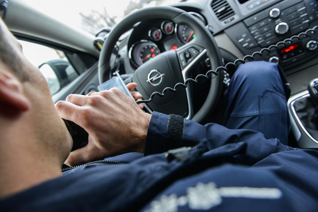Sprawdzanie kierowcy przez policyjne radio wnieoznakowanym radiowozie